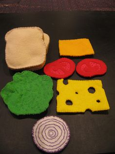 For Christmas last year I made my niece (who is four and just started school) a felt food lunch set. I made enough components so that she could pack different lunches when playing. They were a big hit.  Two slices of bread, swiss cheese, cheddar cheese, two slices of tomato, a leaf of lettuce and an onion!  The lettuce looked better in person. It doesn't sit flat, it crinkles up like real lettuce and has veining embroidered through it.