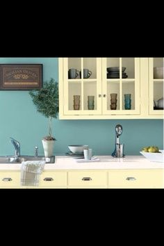 The blue brightens up this kitchen and compliments the cream furniture.