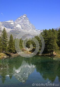 The Mount Cervino (Matterhorn) reflected in the alpine Blue lake (Layet) of Valtournanche, Cervinia, Valle d'Aosta, Italy. This lake derives its name from the blue-green algae in the bottom that gives this emerald green color to the waters. The lake is very cold also in summer.