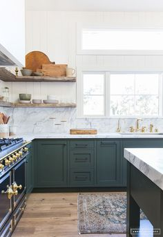 Amber Interiors is another perpetual favorite, and we love this combination of wood and marble with the dark green cabinets! Image via Amber Interiors. Green Kitchen Cabinets, Kitchen Cabinet Colors, Painting Kitchen Cabinets, New Kitchen, Kitchen Dining, Kitchen Decor, Kitchen Ideas, Stylish Kitchen, Dark Green Kitchen