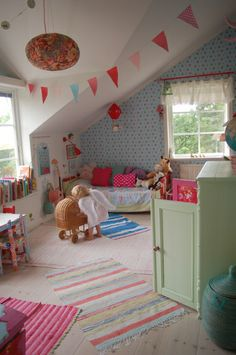 Little bed tucked under slant of ceiling fun, colorful room