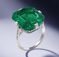 An emerald and diamond ring, by Van Cleef & Arpels, 1920 The octagonal step-cut emerald, weighing 18.67 carats, within a delicate mount millegrain-set with single-cut diamonds and engraved decoration, unsigned, numbered 8752, rubbed French assay mark, ring size M. Estimate: $190,000-230,000
