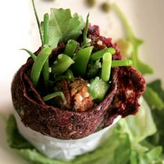 Raw beetroot and celery wrap filled with tomato 'meatballs', greens, onions, pepper and sesame.