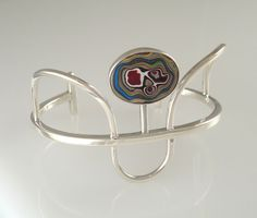 Chic Retro Style Fordite and Sterling Cuff Bracelet from JulieSanfordDesigns on Etsy. Fordite is just so cool.