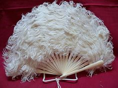 """1890-1900 child's white feather fan with celluloid sticks. The fan measures 11"""" across and is 8"""" deep."""