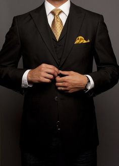 A Black Blazer and Vest offset by a striking Gold tie and pocket square combination