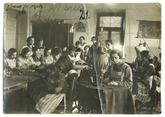 Girls wearing striped aprons pose with sewing machines in a seamstress class at the ORT trade school for girls. Pinsk, 1921.