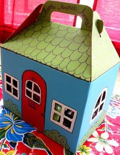 TUTORIAL: DIY Storybook Cottage Doll Carrier. She uses Del Taco food carrier. I would buy a cardboard pet carrier (same shape but sturdier cardboard). I'm thinking Hansel and Gretel candy house or gingerbread house with paper lace doily roof folding over the edge.