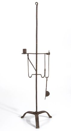 "Wrought iron tabletop candlestand, shaft with curled top, supporting an adjustable friction grip two-arm holder, one for candle and one for rush, raised on a tripod base terminating in scrolled feet. With iron wick trimmers. Probably 18th/19th century. 33 1/2"" H, 9 1/2"" W base."