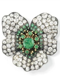 AN ANTIQUE EMERALD AND DIAMOND BROOCH, CIRCA 1890. Modelled as a flowerhead, the circular-cut emerald cluster centre to circular-cut emerald and old-cut diamond petal surround, mounted in silver and gold, later brooch fitting, 3.9cm. #antique #brooch