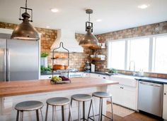 Joanna kept some natural elements in the space, likewall-to-wall bricks and a butcher block-topped island, but she brought in somelight by having Chip enlarge thewindow over the sink and addingwhite cabinetsand stainless steel appliances.