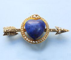 A 15 carat gold brooch with a large lapis heart surrounded by a pearl set snake and an arrow set with rose cut diamonds, the arrow is Cupid's, the son of Venus, goddess of Love, atribute as he sets the fire of love with them. The pearls are Venus' attributes and the snake in combination with a heart means eternity, together: eternal love, circa 1870, England -