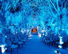 This is an indoor setting, believe it or not. Artificial trees covered with artificial snow, snow-white Victorian style chairs, and blue up-lighting for that icy feel will leave your guests awe-struck!