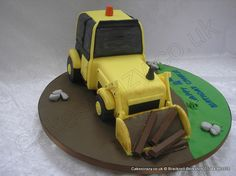 Digger Cake. Mechanical earth moving digger shaped novelty cake finished in the traditional yellow icing with a bucket load of cake and Kit Kats