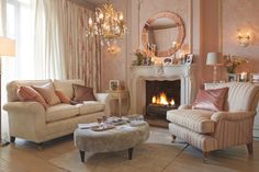 Fabulous glass chandelier, marble fireplace and coral and cream colours - traditional decadence at its best. #interiordesign #livingrooms