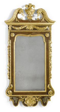 A George II walnut and parcel-gilt mirror circa 1740 the swan's neck cresting centred by Prince of Wales feathers above outset corners with a rectangular mirror plate above a shaped apron, with two candle arms