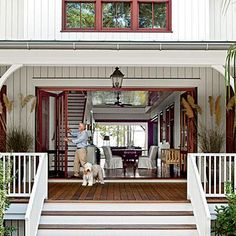 Modern Dogtrot Home | What's a dogtrot home without a porch dog? A shaggy canine beckons guests toward the large folding doors of this Lowcountry home. | SouthernLiving.com