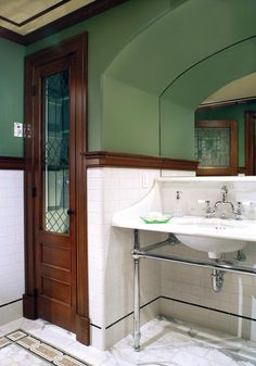 The double sink fits into an arched niche—a clever way of dealing with a low ceiling in this corner of the basement. Beautiful salvaged doors were refitted as closet doors.
