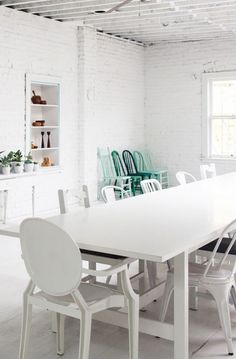 white dining space with painted white brick walls and green dining chairs. / sfgirlbybay