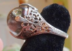 """Circa 1915-1925 Rock crystal """"Pools of Light"""" sterling silver floral filigree ring."""