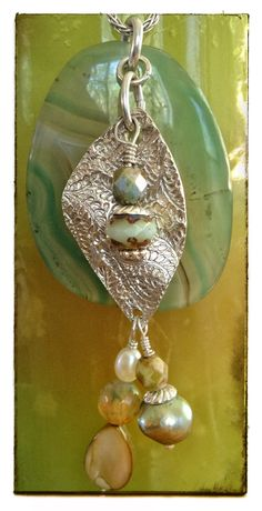 Fine silver pendants with Blue Green Agate background. Sterling silver chains, pearls, semi-precious gems, shells and Czech crystals - hand made by Cilette Swann of Espiritu Fine Art. Email: cece at gypsysoul dot com for stores, custom orders and pricing etc. c) 2013 Espiritu Fine Art