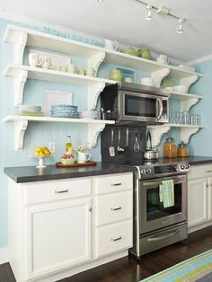 Open shelves! White cabinets, dark gray countertops, stainless steel appliances, yellow wall instead of blue