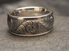 10mm wide titanium hand engraved ring with 14K white gold wrap and standard scroll cross hatch engraving. Please call 817-386-5412 or email reads@erath.net for current pricing