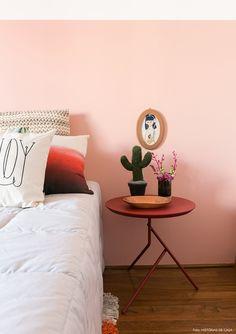 Quarto de adolescente tem parede rosa, almofadas com diversas estampas e mesinha lateral vermelha.
