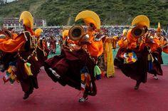 Tibetische Mönche mit festlichen Kostüme tanzen auf der Bühe. Im Tibet Stadtführer vom TIBET REISE EXPERTE wird mehr Informationen über tibetischen Städte, Gebräuche und Regionen vermittelt.