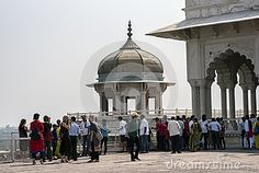 Agra, India - October 11, 2016: Tourists admiring and posing with Samman Burj octagonal tower and Shah Jahan`s private hall Diwan-i-khas of ancient Agra Fort, Agra, India. Agra Fort is a Mughal Architectural Masterpiece.