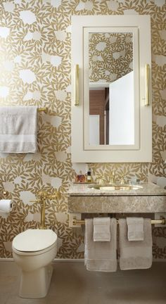 Asuka wallpaper (from Osborne & Little), with its stylized white peonies against metallic gold leaves, sets the tone in this bathroom. The theme continues with luxe gold fixtures, including the towel bar and cabinet pulls.