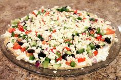 """Mediterranean """"7 Layer"""" Dip    ◦16 ounces plain hummus (this is the large size container, and I didn't use it all – for a smaller crowd I'd say you could get away with 8 ounces.  I used plain and I thought the dip still had plenty of flavor)  ◦8 ounces tzatziki (a Greek yogurt/cucumber sauce)  4-6 ounces crumbled Feta cheese Assorted chopped vegetable toppings: I used black olives, tomatoes, cucumbers, bell pepper and red onion.  Olive oil and black pepper  Pita chips or pita wedges, to…"""