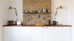 This bare brick wall adds charisma to this small but compact kitchen in an Islington studio