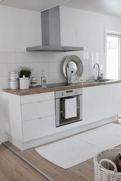 Tiny white contemporary kitchen with wooden countertop, no upper cabinets, white rug, solid wood floors, white tile splash back. Kitchen Inspirations, White Contemporary Kitchen, Home Kitchens, Kitchen Remodel Small, Kitchen Splashback, Kitchen Design, Kitchen Dining Room, Small Modern Kitchens, Contemporary Kitchen