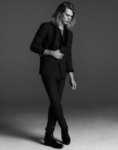 Austin Butler wearing a suit and standing with his legs crossed