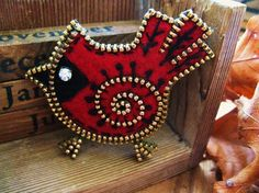 "This chubby little cardinal is made with recycled sweater felt. Bird is enveloped with pieces of thrifted brass zipper. The cardinal has been further embellished with hand embroidery... running stitches and french knots. A rhinestone was used for the eye.The aprox. dimensions of the bird are 2"" x 2 1/2"".This brooch is light weight and quite firm."