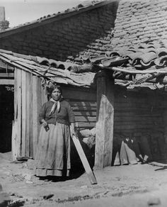 Native American woman standing next to the San Fernando Mission. The San…