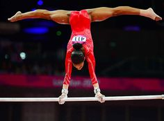 American gymnast Gabby Douglas performing handstand on uneven bars at 2012 Summer Olympics in London, England.
