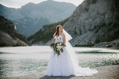 For this summer mountain wedding in Canmore we went to Whitemans Pond in Canmore for the couple's wedding photos. The bride had a gorgeous bouquet for her wedding photos. The bridesmaids had a gorgeous light blue dress and the groomsmen had a dark navy suit to match. To see the full wedding day at the Canmore Nordic Centre visit Teller of Tales Photography.  #weddingphotos #weddingideas #canmorewedding #mountainwedding #summerwedding #bluebridesmaiddress Pond Wedding, Summer Wedding, Bridesmaids, Bridesmaid Dresses, Wedding Dresses, Wedding Couples, Wedding Photos, Light Blue Dresses, Disney Couples