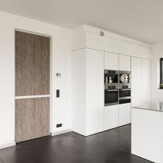 Moderne binnendeuren op maat met houtafwerking naast een witte keuken