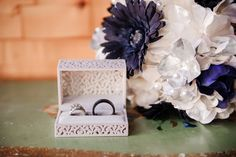 bride and grooms wedding rings in a white lace box with a bouquet of flowers with their colors sitting on an antique end table in the bridal suite (Tracy Shoopman Photography)