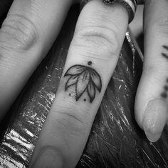 Lotus flower finger tattoo by Clara Welsh