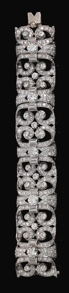 DIAMOND BRACELET, CIRCA 1930. Composed of a series of articulated panels of scroll design, set with circular-cut and baguette diamonds, length approximately 190mm.