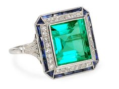 Picture perfect Art Deco flair dares to impress with an exceptional rectangular cut natural emerald at its heart. Superb color and clarity with very few inclusions read clear to the eye brings an estimated 5.25 carats of bold color to the forefront. Set in platinum, circa 1925