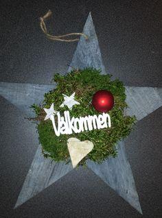 """Dörrdekoration i trä. Dekorerad med mossa, näverstjärnor, julgranskula och stick med texten """"Välkommen""""."""