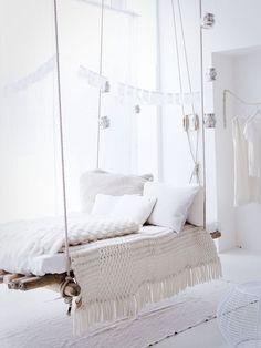 Highlight des schlichten weißen Zimmers ist die Indoor-Schaukel. Gemütliche Sitzgelegenheit mit weißen Kissen und einem flauschigen Decke. Tolle Wohnidee für hohe Räume.