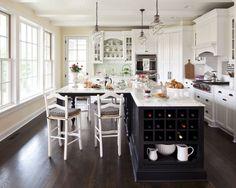White kitchen with dark floors and dark island. Martha O'Hara Interiors