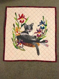 I made this wall hanging quilt in memory if my beloved cat Alex. It's hand appliqué with machine quilting that uses variegated thread. I love it! It is a very good likeness to Alex. He loved to sit on a cushion in the sun. The irises are my favourite flowers. I miss him so much.