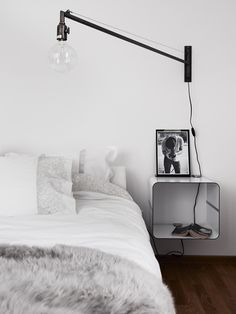 Bedroom - Floating cube bedside table, industrial light, and grey fur throw.