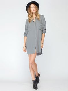The Gentle Fawn Voyage Dress is a button up shirt dress. It has nine button closure going up the front and a collar. It has 2 pockets on the front-one on each side. It has long sleeves and a pleat on